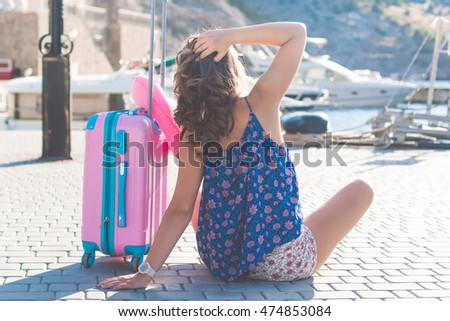 Girl is sitting with pink suitcase