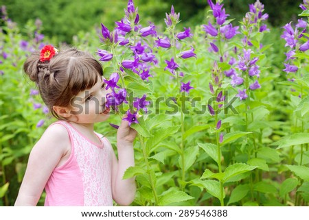 girl is smelling flowers in the Park - stock photo