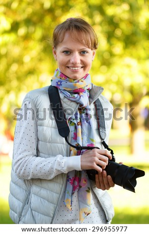 Girl is smiling and keeping camera on foliage background in bright sunlight