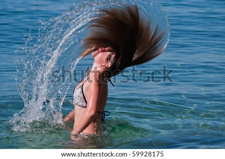 Girl is splashing water with her hair