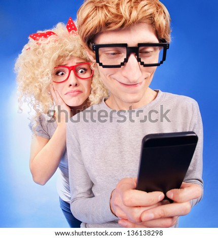 Girl is spying on boyfriend he is using a smart phone - stock photo