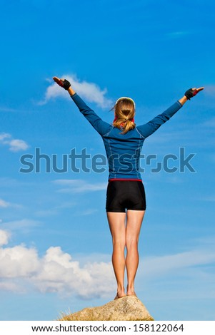 Girl is standing on top of the rock and enjoying the view  - stock photo
