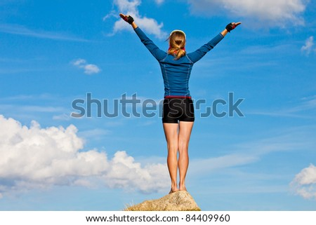 Girl is standing on top of the rock and enjoys sun. Her hands are raised up - stock photo