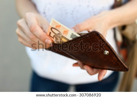 Girl is taking out a banknote of fifty euros from brown leather wallet on the street. Hands, money and wallet close-up - stock photo