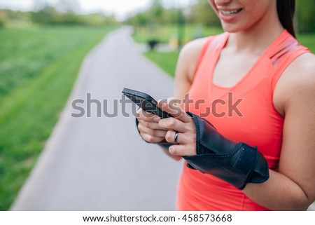 Girl is using mobile phone after workout. Close up