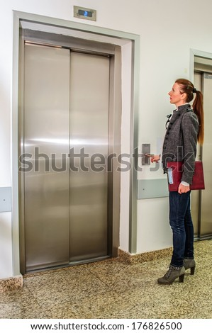 Girl is waiting for an elevator in a building