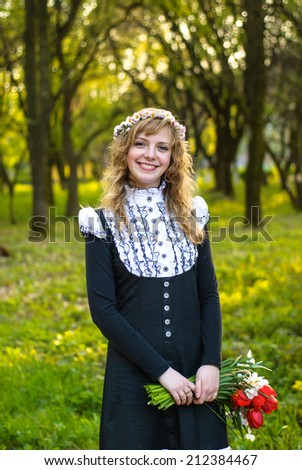 Girl is walking in the park. Cute woman with flowers