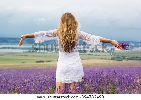 Girl is wearing white dress at purple lavender field - stock photo