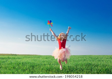 girl jumping and  holding a toy flower - stock photo