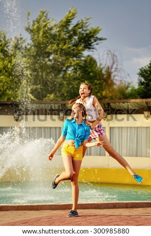 Girl jumping, holding the shoulders of her best friend, near the fountain in the summer park. Girls dressed in shorts and a shirt. On summer vacation. The concept of true friendship. - stock photo