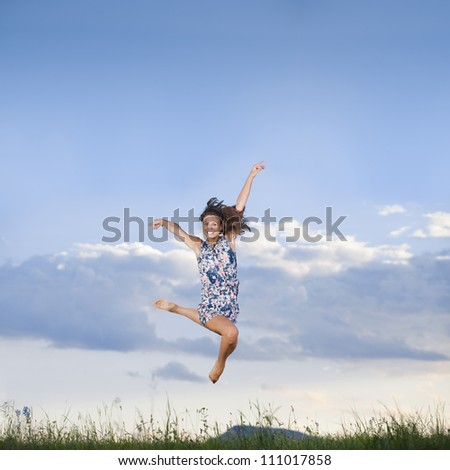 girl jumping in a meadow - smiling face and arms raised - stock photo