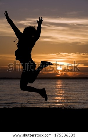 Girl jumping in sunset with beautiful colors