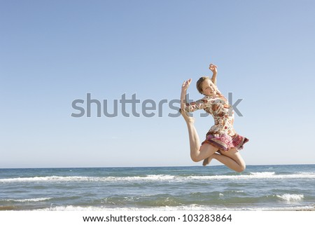 Girl jumping in the air on a beach's shore, with a blue sky in the background. - stock photo