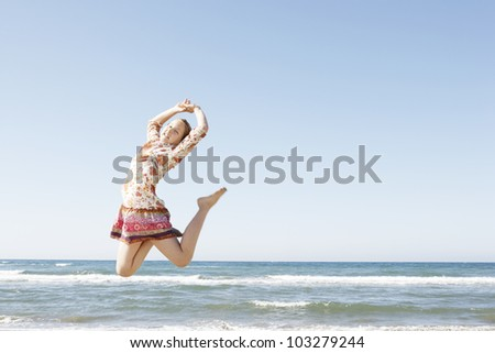 Girl jumping in the air on a beach with a blue sky in the background. - stock photo