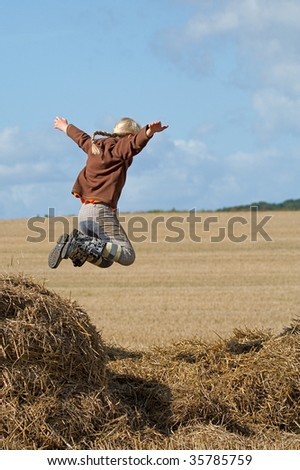 Girl jumping in the haystack - stock photo