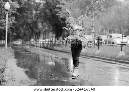 girl jumping in the puddles in the autumn rain