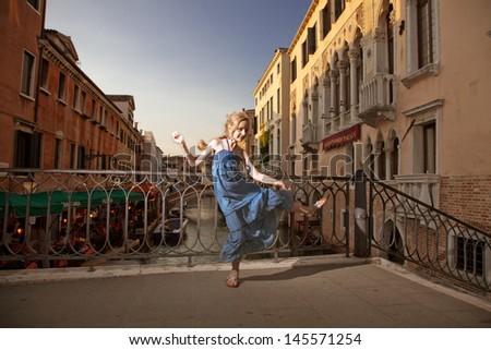 Girl jumping in Venice - stock photo