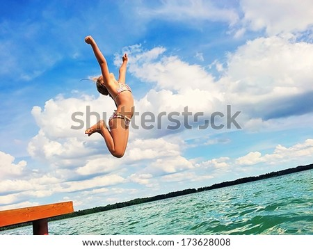 Girl jumping into the lake. - stock photo