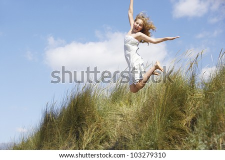 Girl jumping off a long grass hill on the beach, with a blue sky in the background. - stock photo