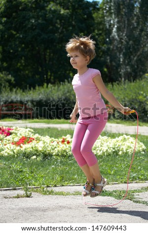 Girl jumping on a skipping rope in the park.