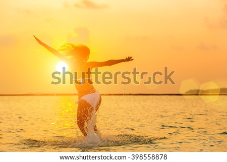 Girl jumping on the beach at sunset