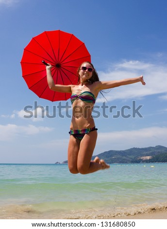 girl jumping on the beach with a red umbrella - stock photo
