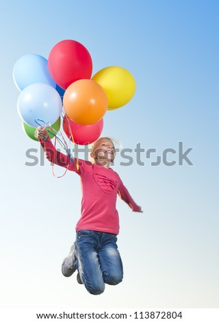 Girl jumping outside with balloons