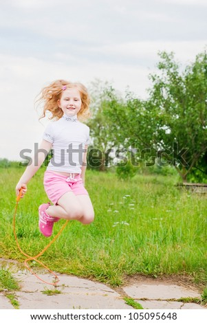 girl jumping over a skipping rope - stock photo