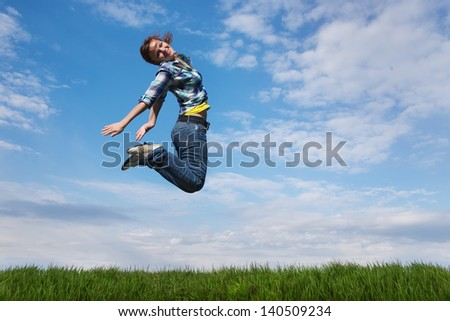 girl jumping over the field with green grass - stock photo