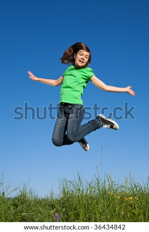 Girl jumping, running on green meadow against blue sky