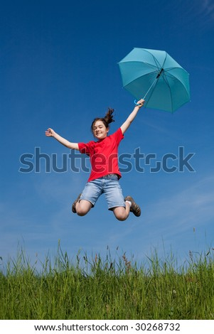 Girl jumping, running, with umbrella on green meadow