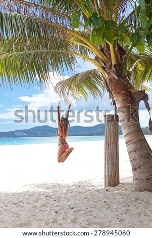 Girl jumping under palm tree on a tropical beach at summer - stock photo