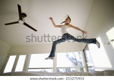 Girl (11-13) jumping up and down on bed, mirroring shape of electric ceiling fan, smiling, portrait, low angle view