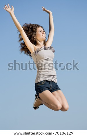 Girl jumping. Young brunette jumping on background of sky