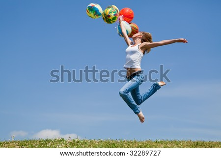 Girl jumps on a green grass with balloons in a hand