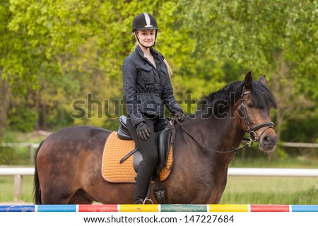Girl jumps with her brown horse (New-Forest-Pony) over an obstacle - stock photo