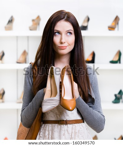 Girl keeps two shoes in the shopping mall and can't choose the one for her - stock photo