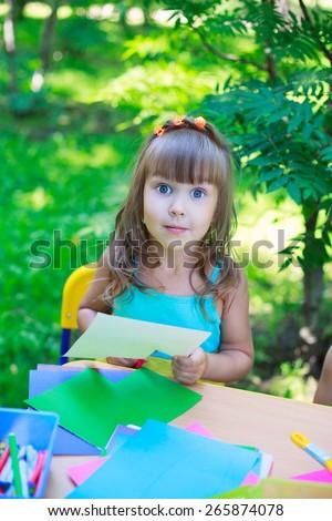 Girl, kid, child,  schoolgirl preschooler cutting multicolored paper outdoors, classroom playing in the garden - stock photo