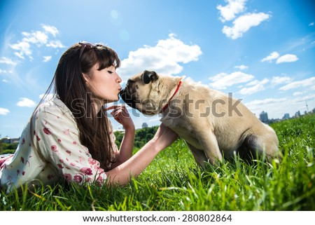 Girl kissing dog breed Mops - stock photo