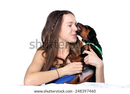 Girl kissing her doberman puppy isolated on white background - stock photo