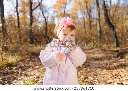girl kissing her toy mouse in park - stock photo