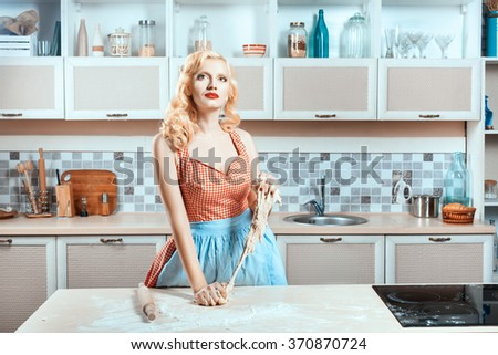 Girl kneads dough in the kitchen and dreams. She is preparing dinner in the kitchen near the stove. - stock photo