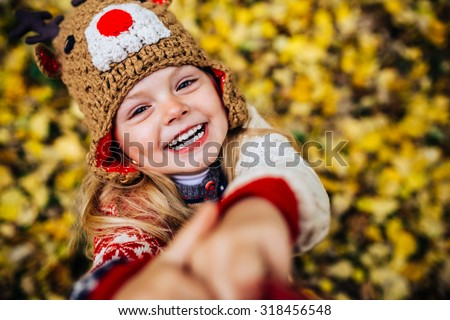 girl laughing at the camera on a background of yellow leaves