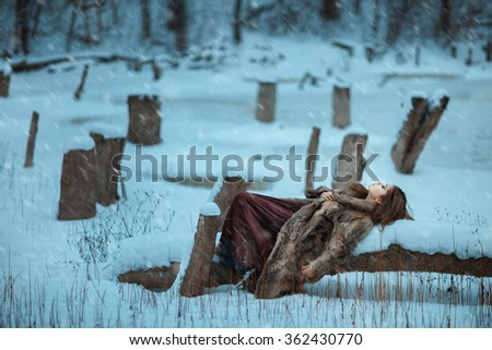 Girl lay on a tree and freeze in winter. She is alone in the woods among the drifts of snow. - stock photo
