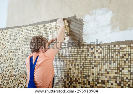 Girl laying ceramic tiles of the mosaic. Renovated apartment - stock photo
