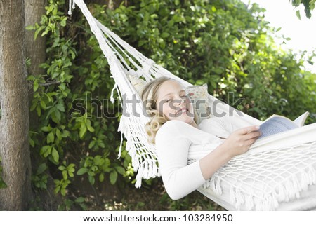 Girl laying down on a hammock in the garden, reading a book and smiling. - stock photo