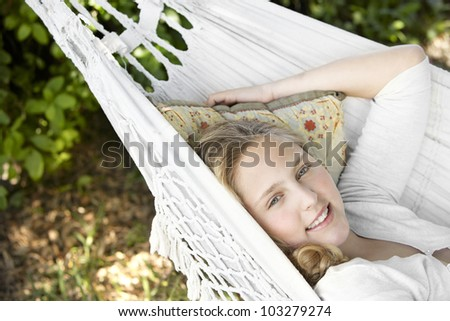 Girl laying down on a hammock in the garden, smiling. - stock photo