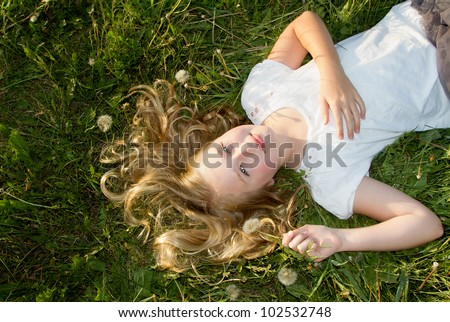 Girl laying in a grassy field with dandelions - stock photo