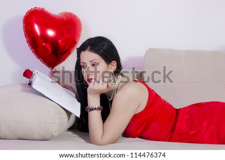 Girl laying on bed reading love stories - stock photo