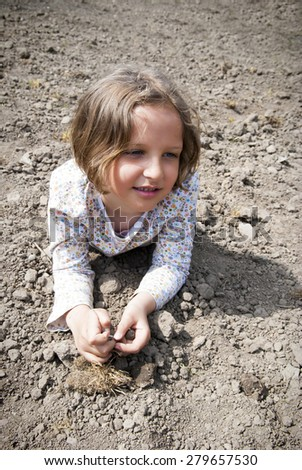 Girl laying on soil during preparation to plant.